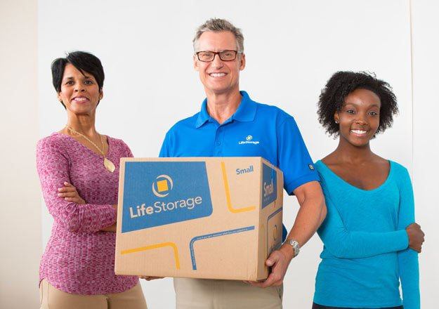 Life Storage manager holding box next to two customers