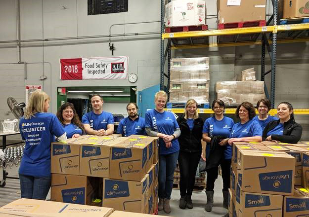 Life Storage employees volunteering and posing with boxes