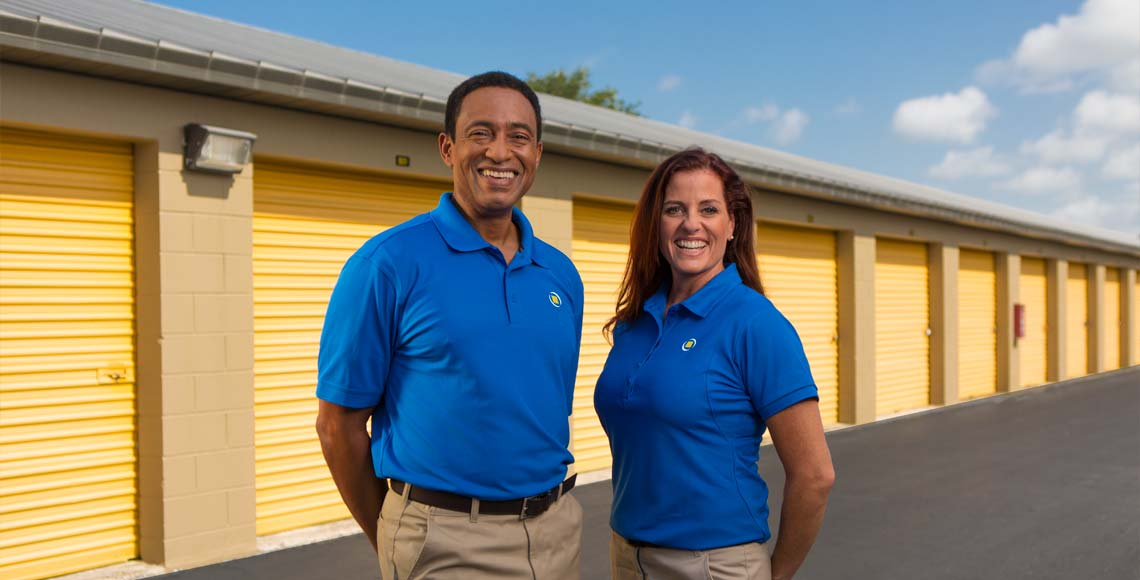 Managers standing in front of storage units outside