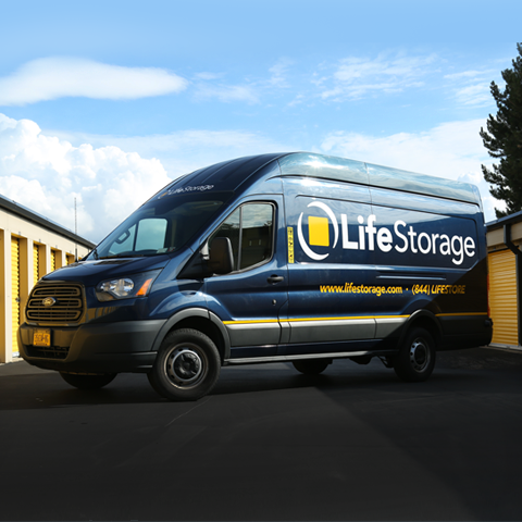 Blue Life Storage Van parked in front of storage facility.