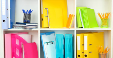 white bookshelf yellow blue pink binders school supplies