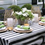 A basket of flowers flanked by twin lanterns makes a great quick and simple outdoor centerpiece.