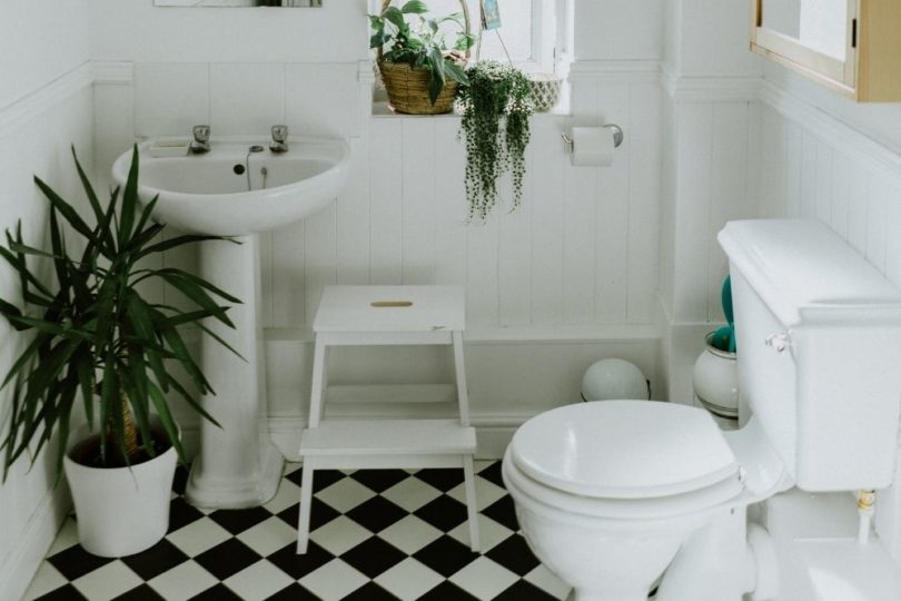 Organized Kids Bathroom with Step Stool and Black and White Floor Tiles