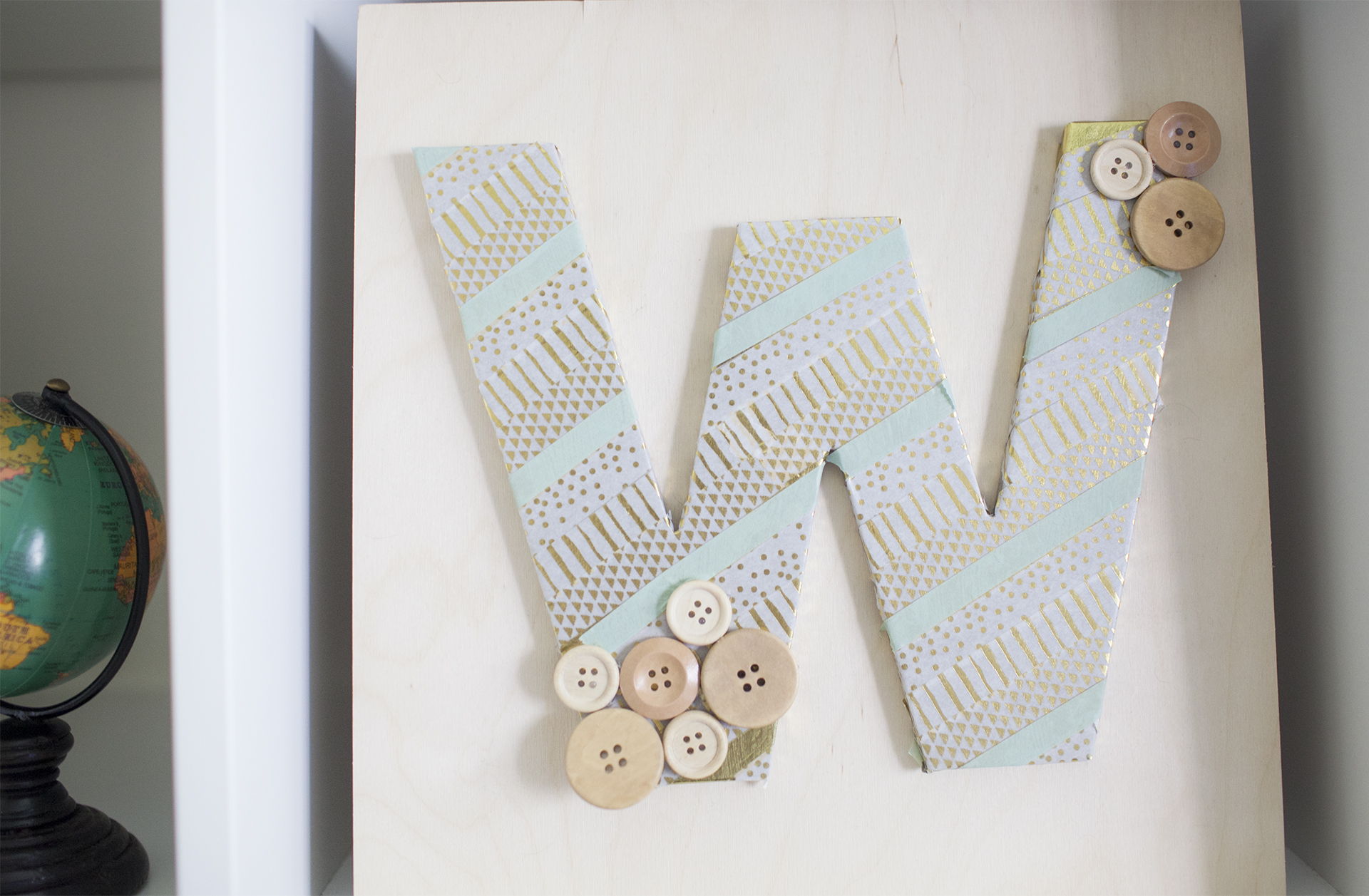 Craft a personalized monogram using Washi Tape. This DIY can be customized for a children's room, living room, or office.
