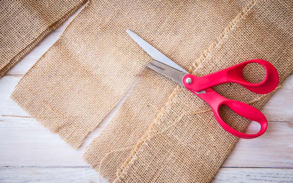 red scissors cutting burlap