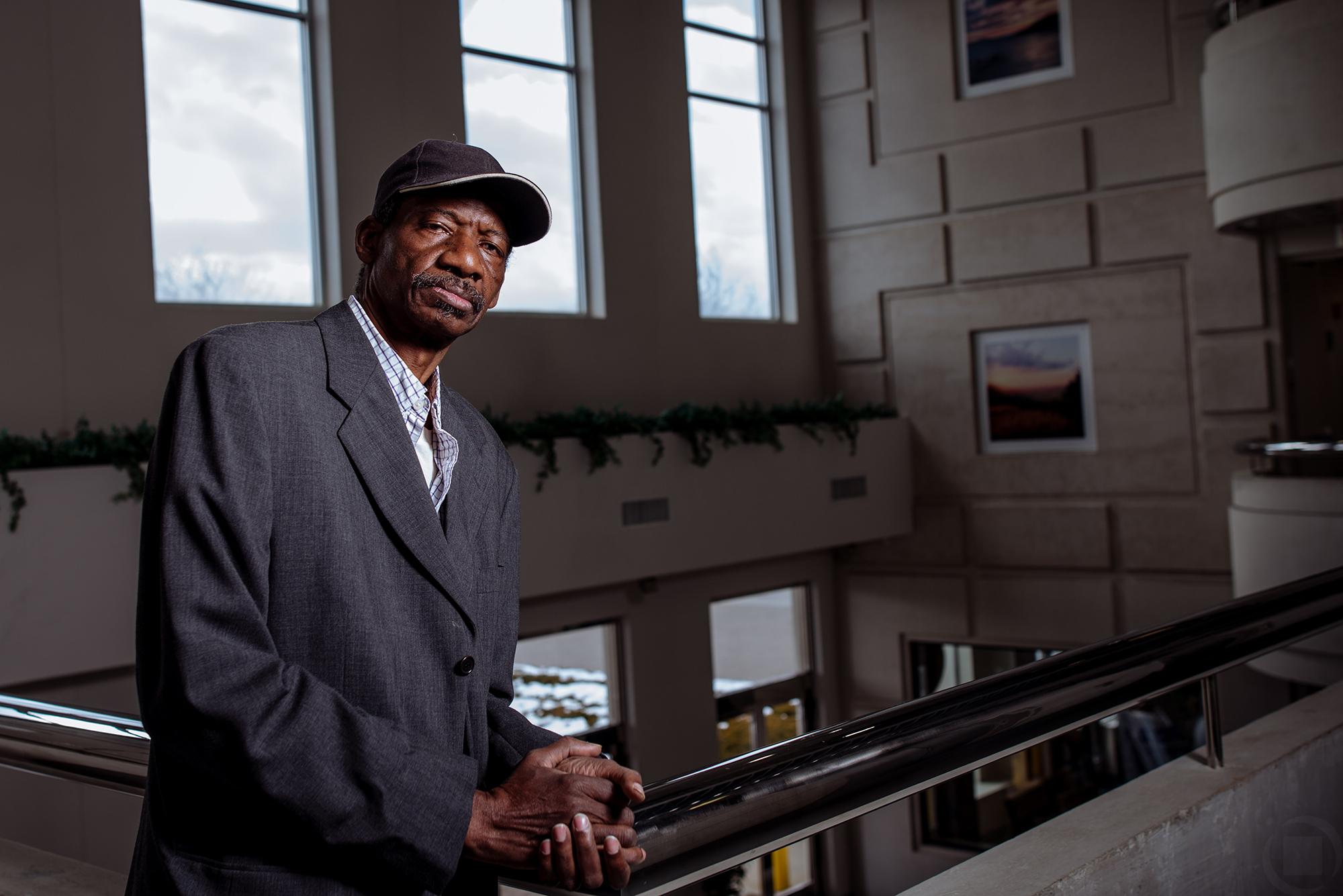 balcony african american man baseball hat suit coat