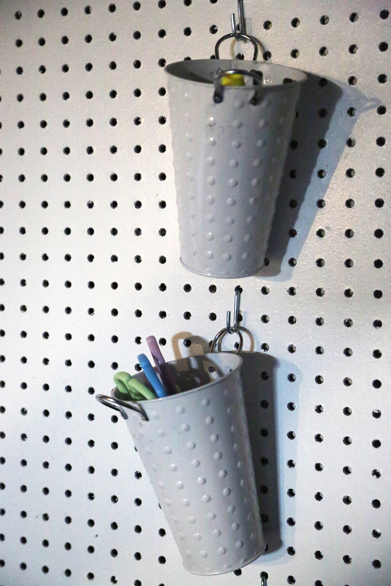 white pegboard scissors hanging bucket