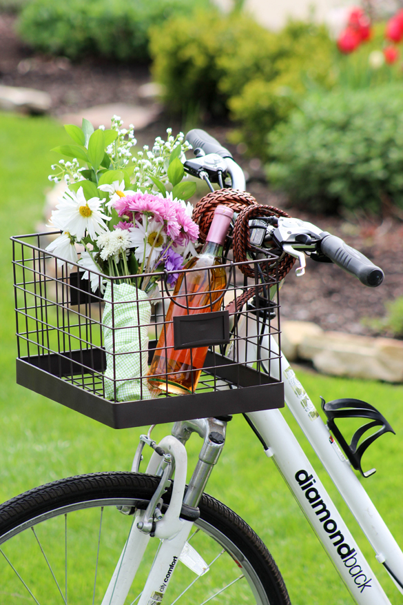 diy bike basket made with braided belts and wire basket filled with flowers