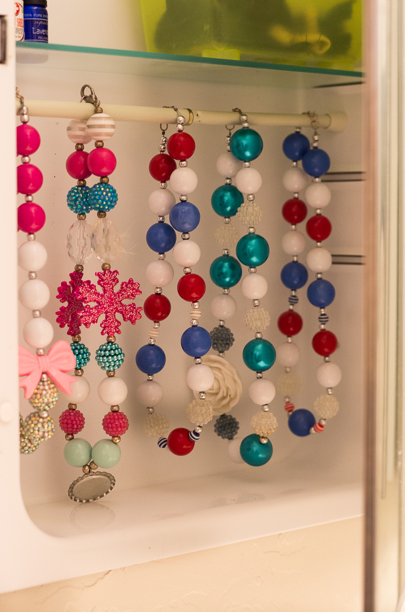 Bathroom Organization Ideas: a tension rod inside a medicine cabinet creates a storage place for necklaces