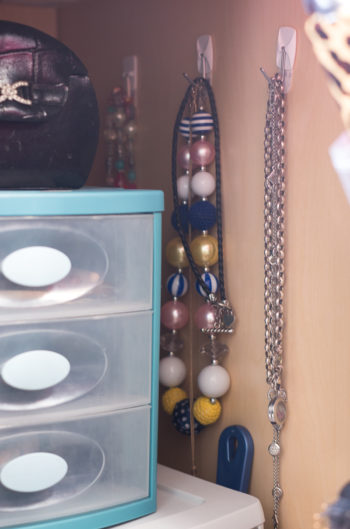 Bathroom Organization Ideas: Command hooks on the inside of a vanity cabinet to hang jewelry
