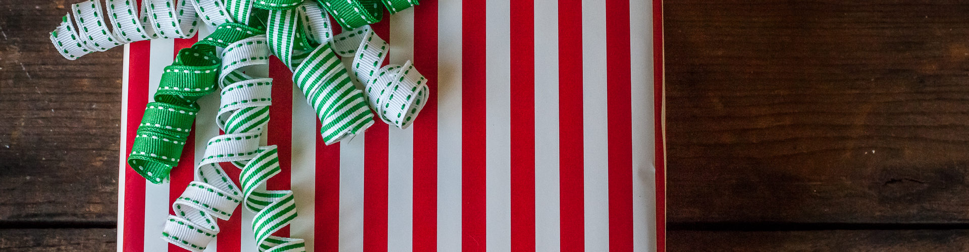 Gift wrapping station organization ideas red white striped present green ribbon bow