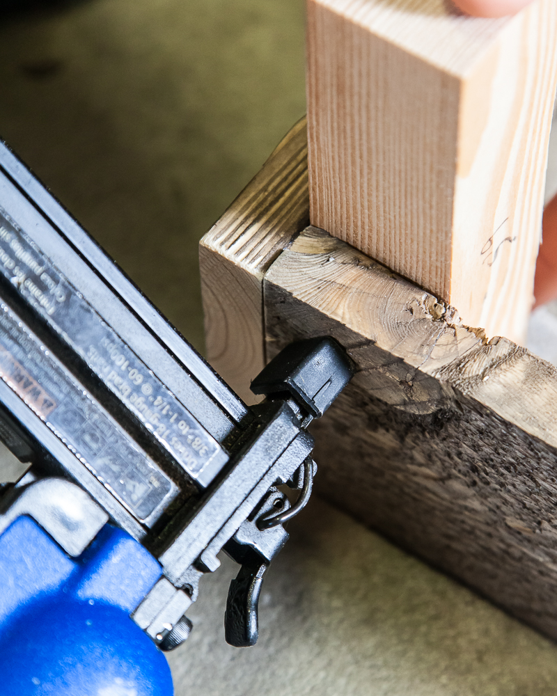 nail gun inserting nail into plywood on diy storage ottoman
