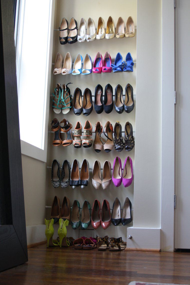 DIY closet organization ideas on a budget: use tension rods to create tons of storage space for shoes and other items.