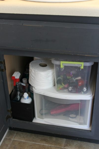 This unorganized space under the bathroom sink becomes functional with one of our small bathroom storage ideas: DIY shelves.