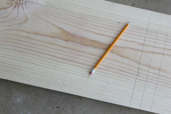 Dimensions for a DIY under-the-sink shelf written in pencil on wood, part of our favorite small bathroom storage ideas.