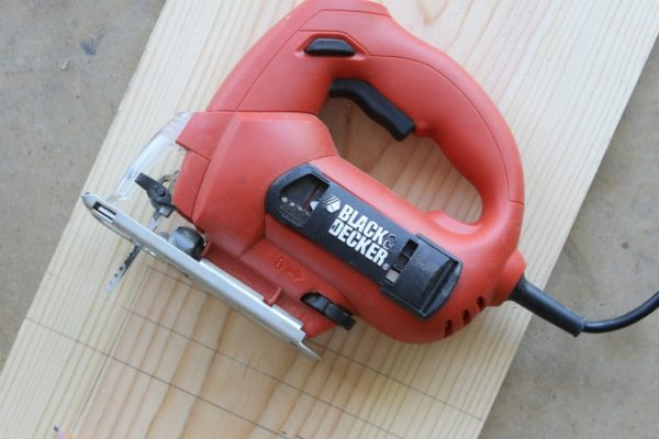 """Use a jigsaw to cut two 2"""" wide pieces of wood as deep as you want your DIY under-the-sink shelves, part of our favorite small bathroom storage ideas."""
