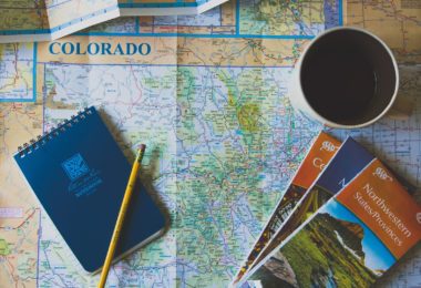 Best cities to move in Colorado: maps, passport, pencil, cup of coffee in preparation to relocate