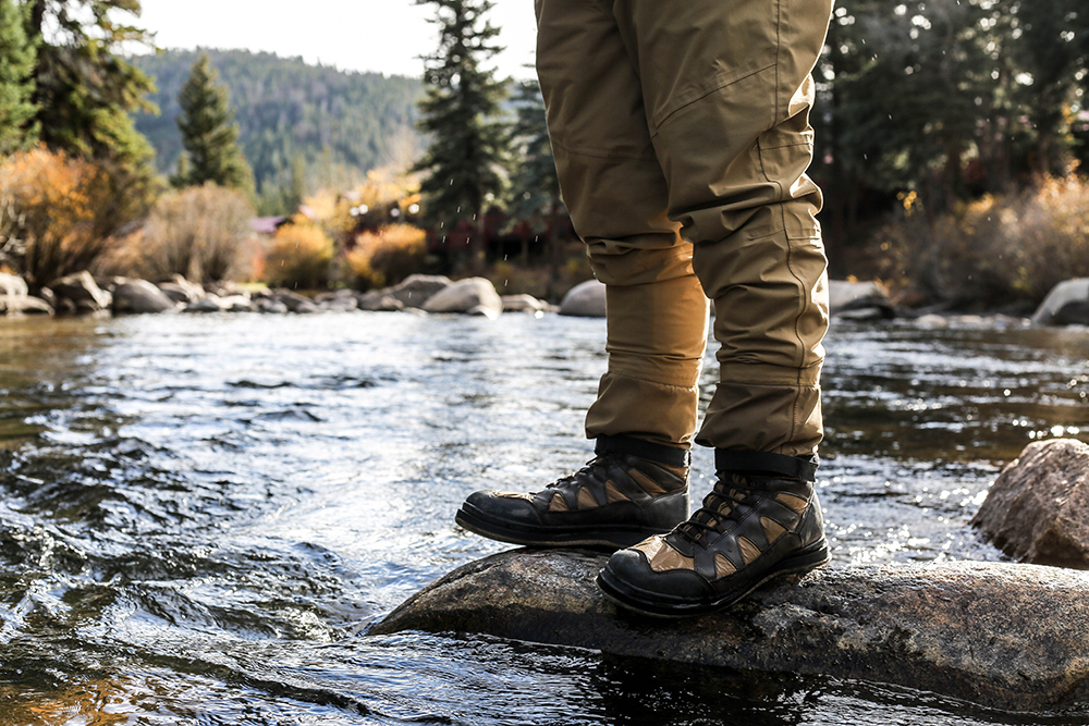 Best cities to live in Colorado: hiking boots on rocks in the middle of the running water