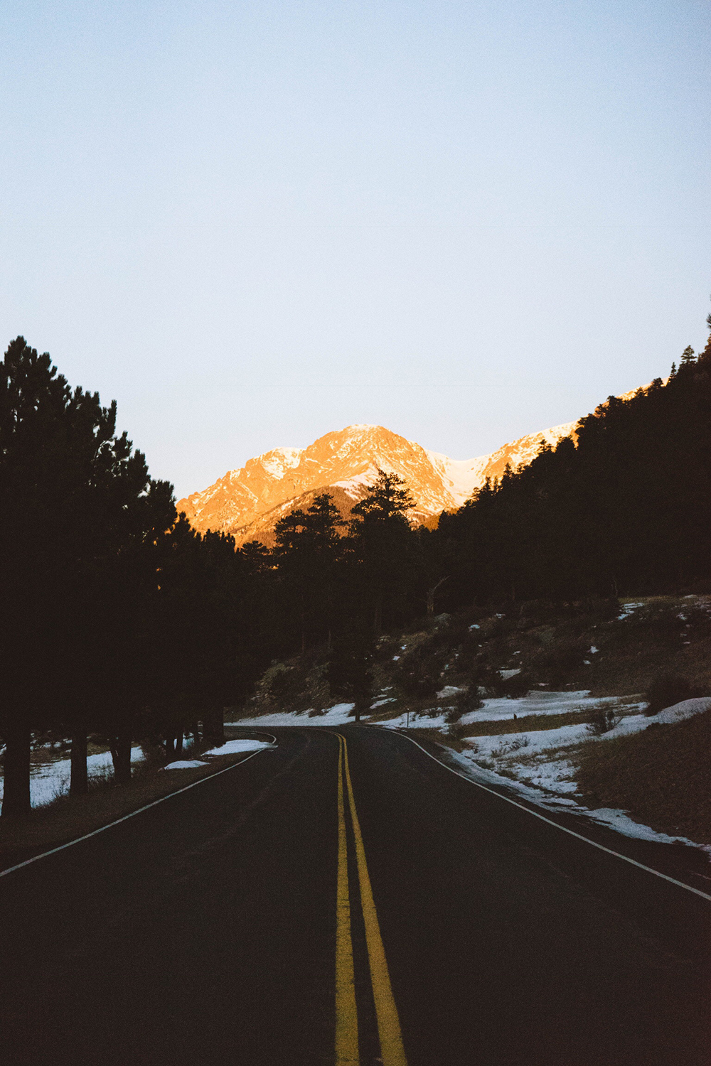 Best cities to live in Colorado: setting sun on mountain with snow adorning the highway