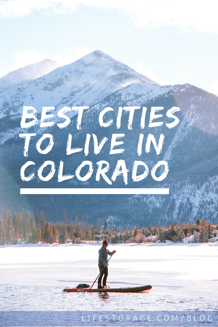 Best places to live in Colorado: woman kayaking in the water with mountains behind