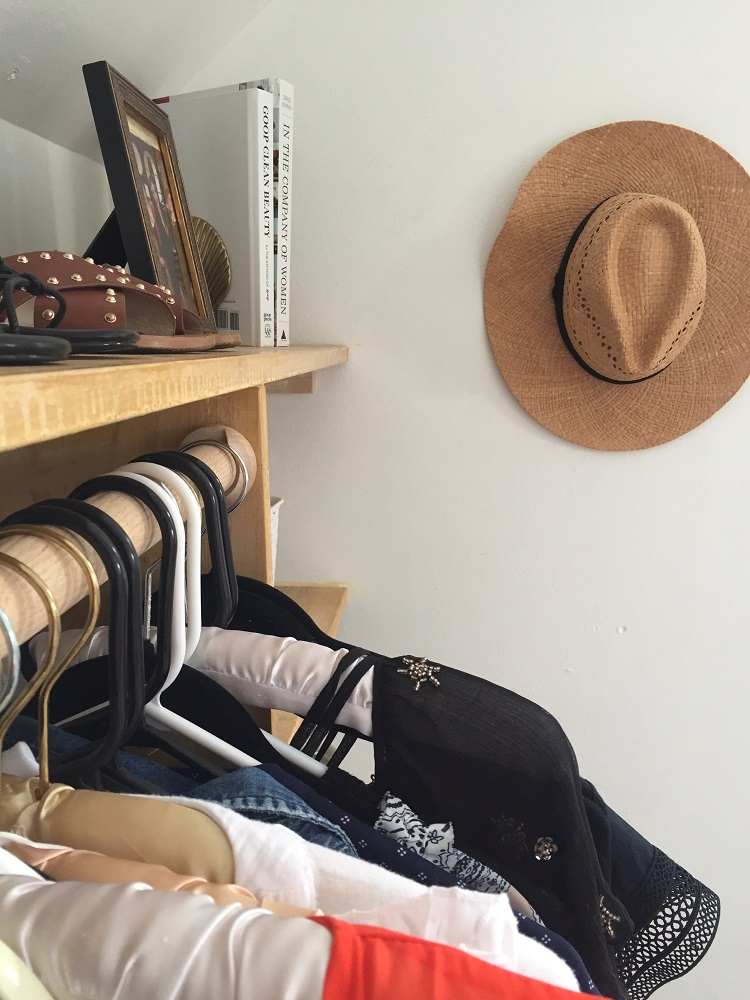 DIY Dressing Room: view of clothes in closet and picture frame on shelf with hanging hat