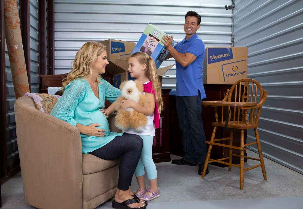 10x15 Storage Unit - Family inside of unit with furniture and boxes