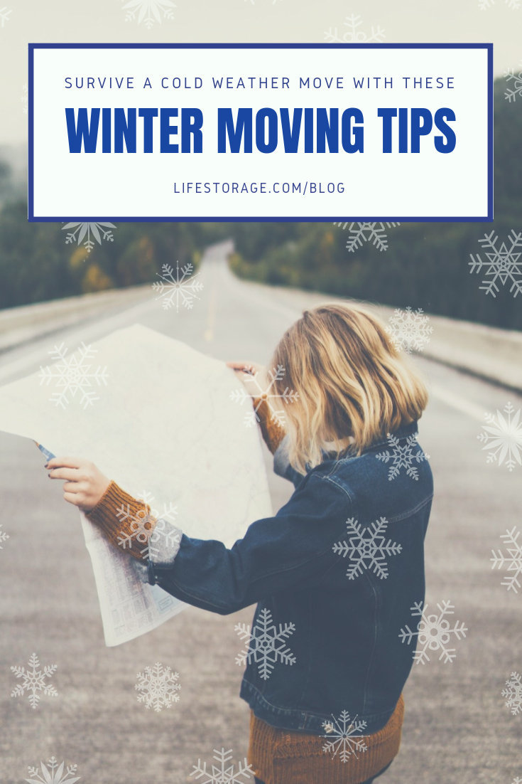 Survive a cold weather move with these winter moving tips - girl holding map outside dressed in warm clothes